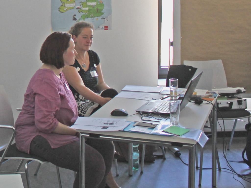 Zwei Referentinnen mit Laptop und Anschauungsmaterial an einem Tisch vor Publikum