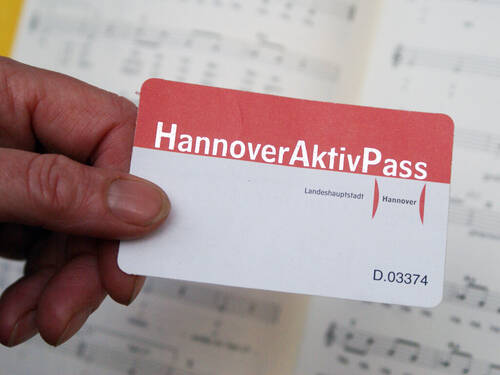 In the foregrond there's a hand holding the red-white Hannover-Aktiv-Pass card, in the background are sheets of music.