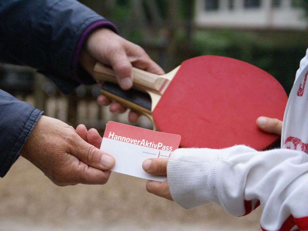 Die Hände von einem Erwachsenem und einem Kind tauschen den Hannover-Aktiv-Pass und zwei Tischtennisschläger aus