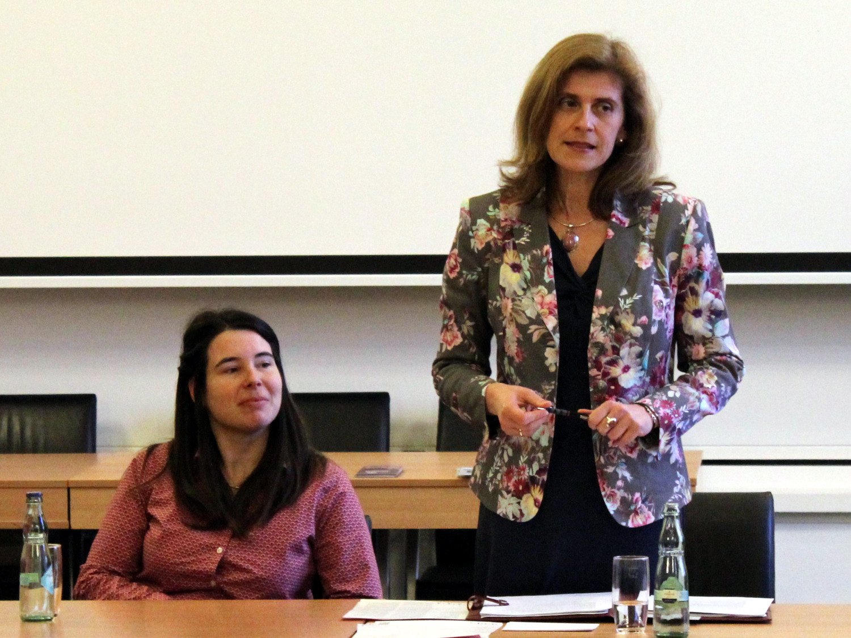 Eine Person sitzt hinter einem Tisch im Gobelinsaal, eine weitere person steht rechts daneben und spricht.