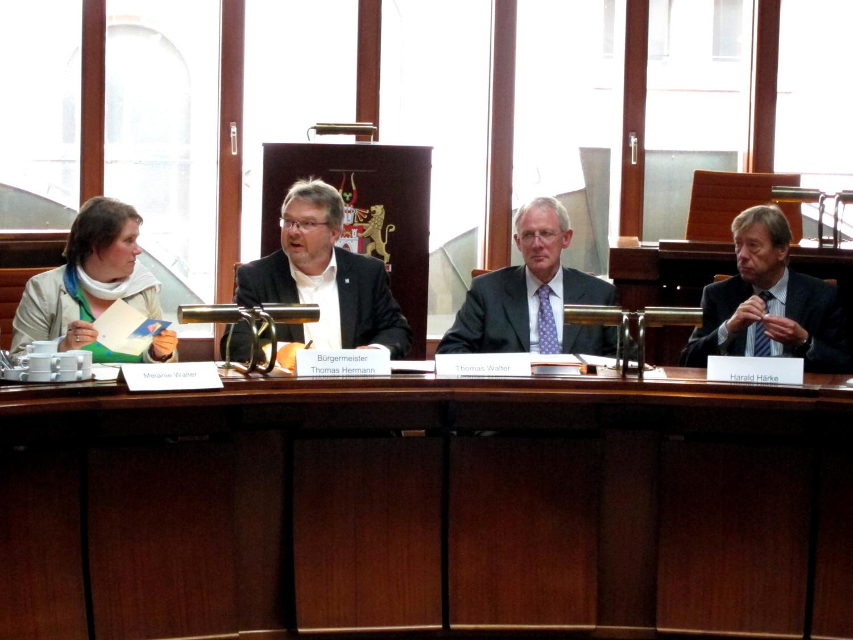 Vier Personen sitzen hinter Pulten. Die beiden links schauen sich an.
