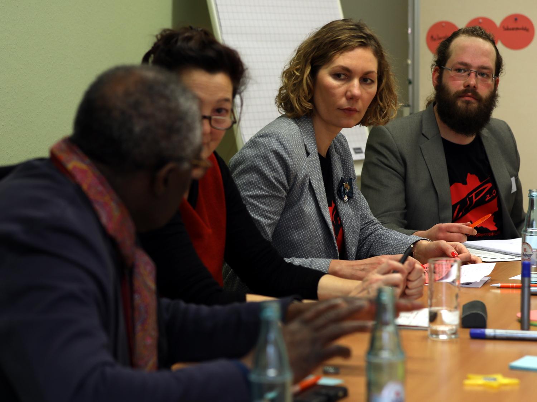 Vier Personen - zwei Männer und zwei Frauen - sitzen in einer Stuhlreihe in einem Raum des Huases der Jugend an Tischen. Der Mann links im Bild spricht, die drei anderen Personen blicken zu ihm.