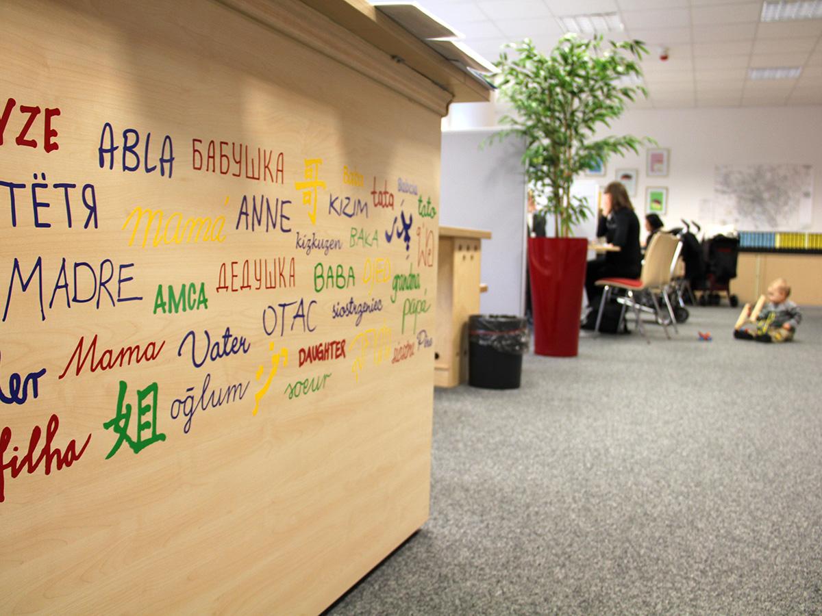 Ein Empfangstresen im Familienservicebüro, auf dem Verwandtschaftsbezeichnungen in unterschiedlichen Sprachen zu sehen sind. Im Hintergrund eine Beratungssituation, bei der ein Kleinkind auf dem Fußboden spielt.