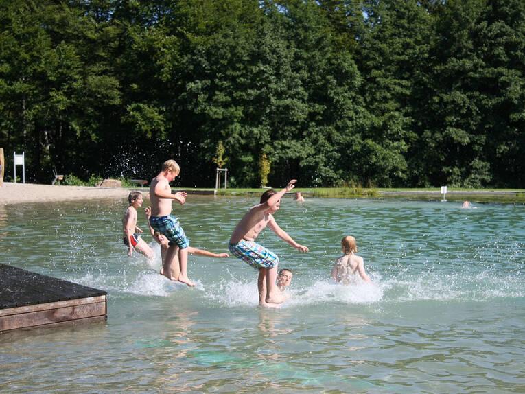 Jugendliche springen mit Anlauf in einen See