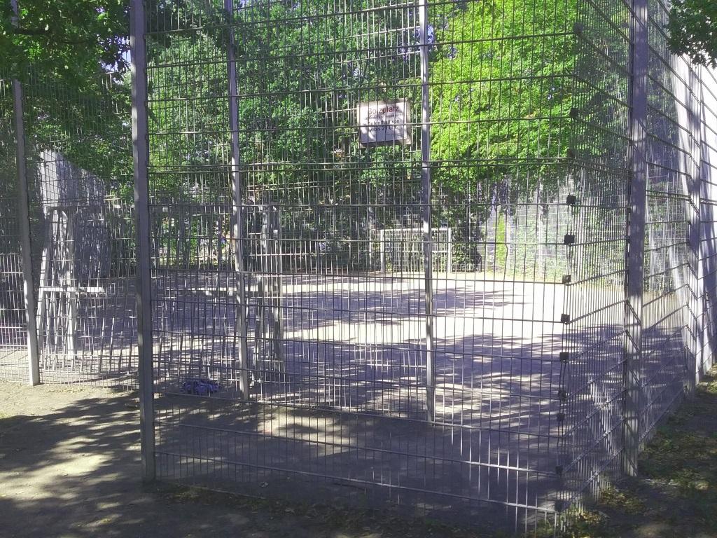 Der Bolzplatz Döhrener Mühle liegt unter Bäumen und ist von einem hohen Ballschutzgitter umgeben.