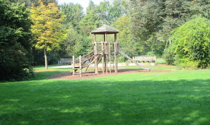 Spielplatz mit großer Rasenfläche und Holzspielgerät