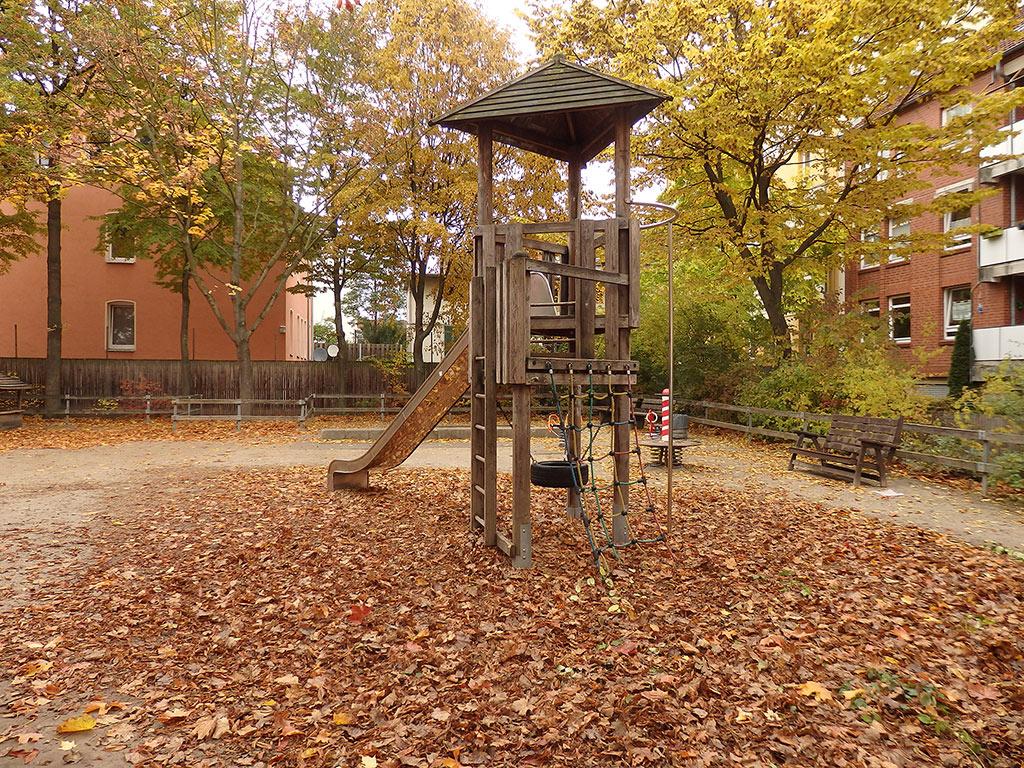 Holzspielgerät mit Rutsche auf einem herbstlichen Spielplatz