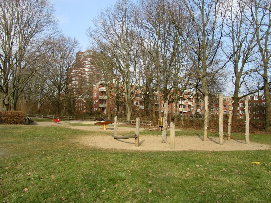 Spielplatz mit Klettergerüst, Wippschaukel und Drehteller vor Wohnsiedlung