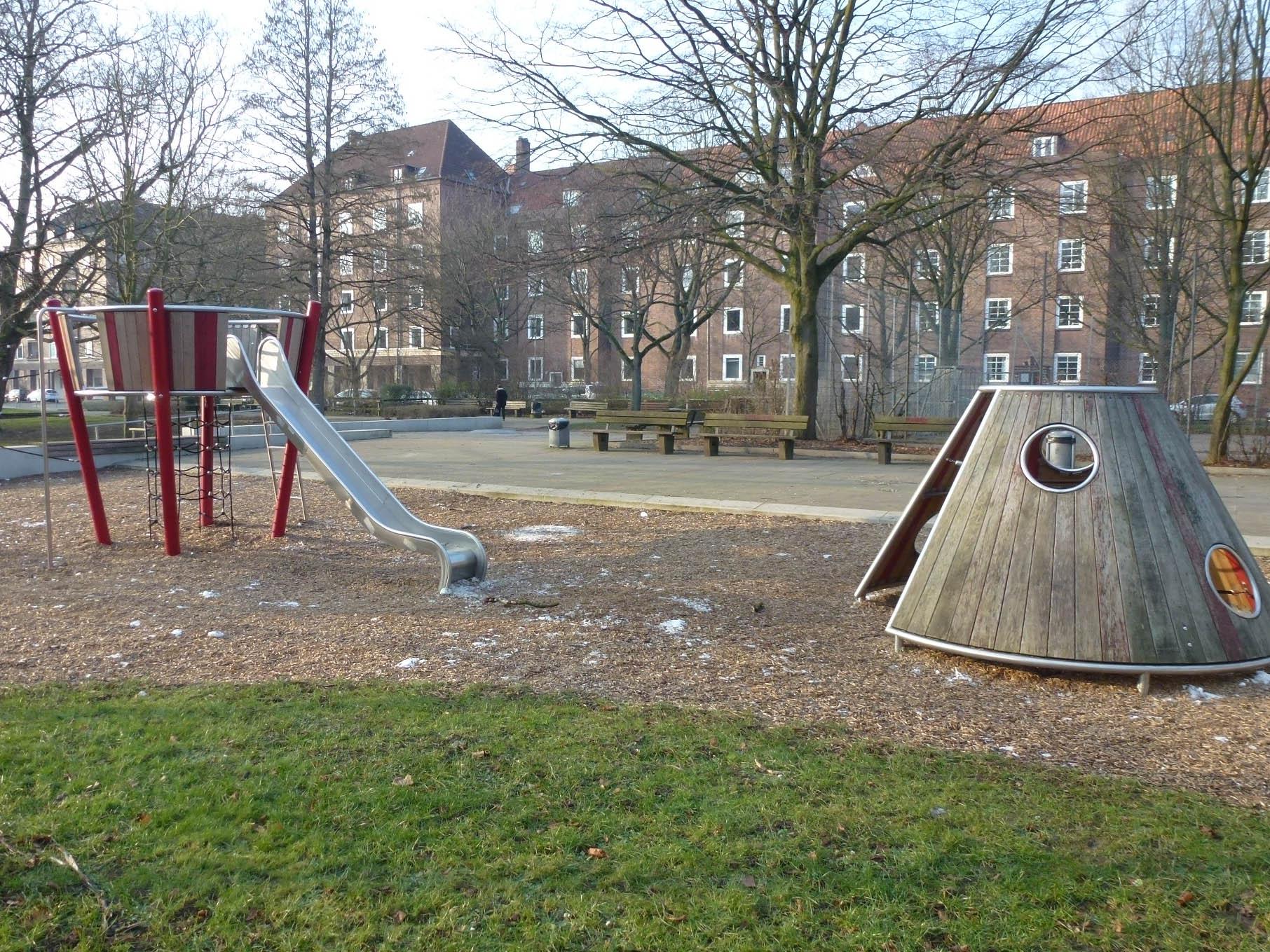 Spielplatz mit einer Rutsche und einem Häuschen.