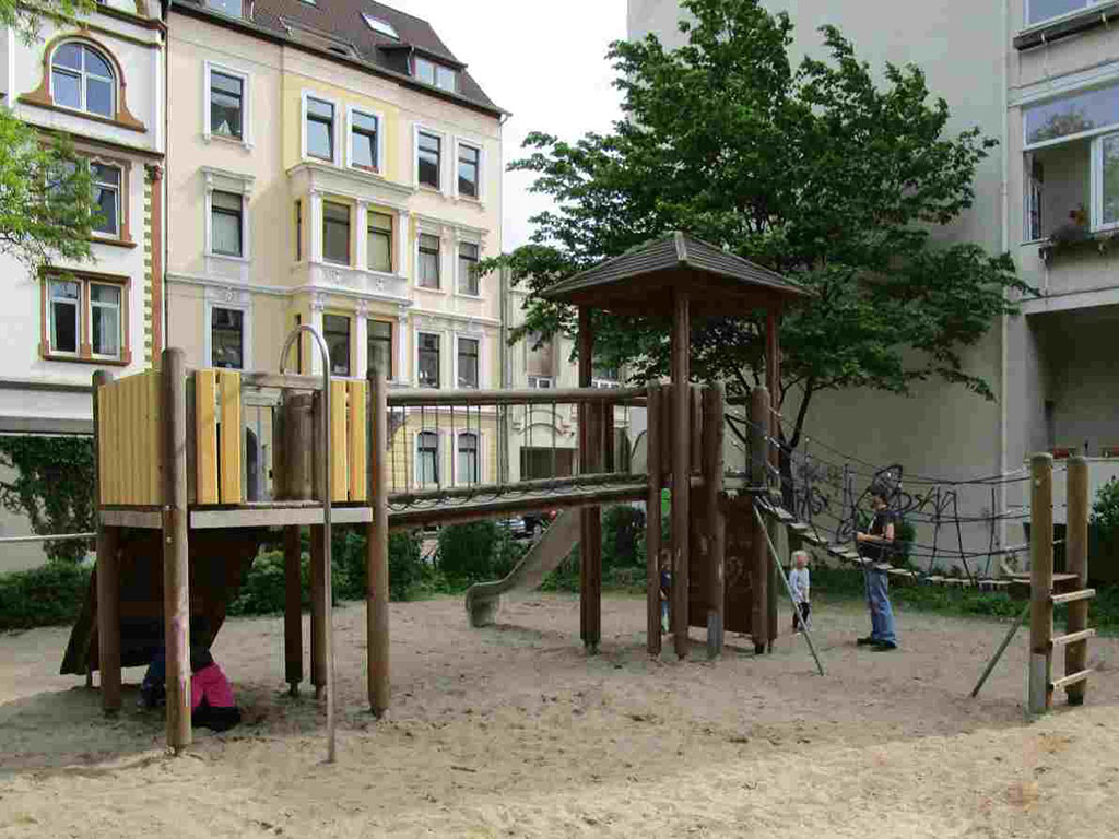 Ein Holzspielgerät mit Rutsche und Klettermöglichkeiten auf dem Spielpatz Gerberstraße