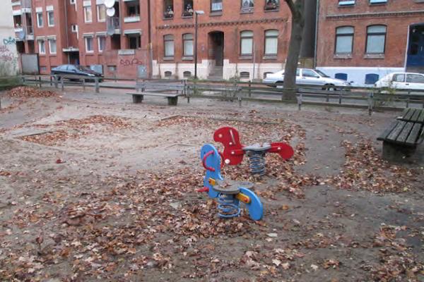 Sandkasten und blaues und rotes Schaukelpferd auf Sandboden