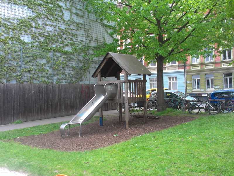 Holzhus mit Metallrutsche auf grüner Wiese