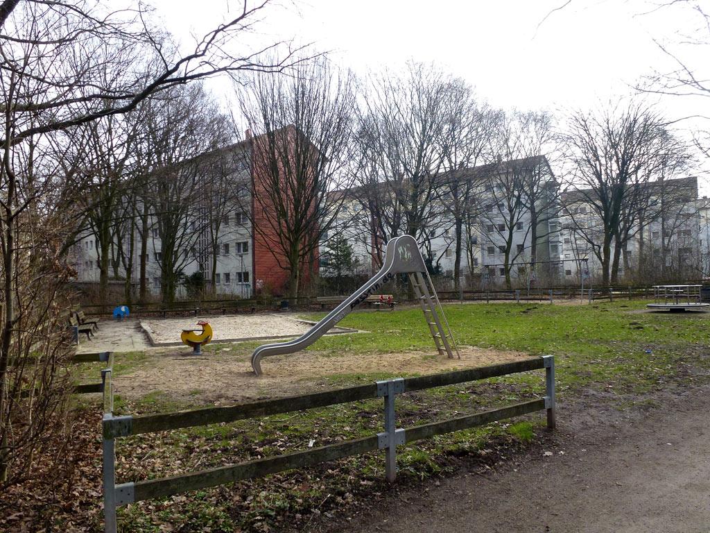 Im Vordergrund eine Rutsche und ein Wippgerät, im Hintergrund ein Sandkasten und ein Drehteller sowie Sitzbänke und Wohnhäuser