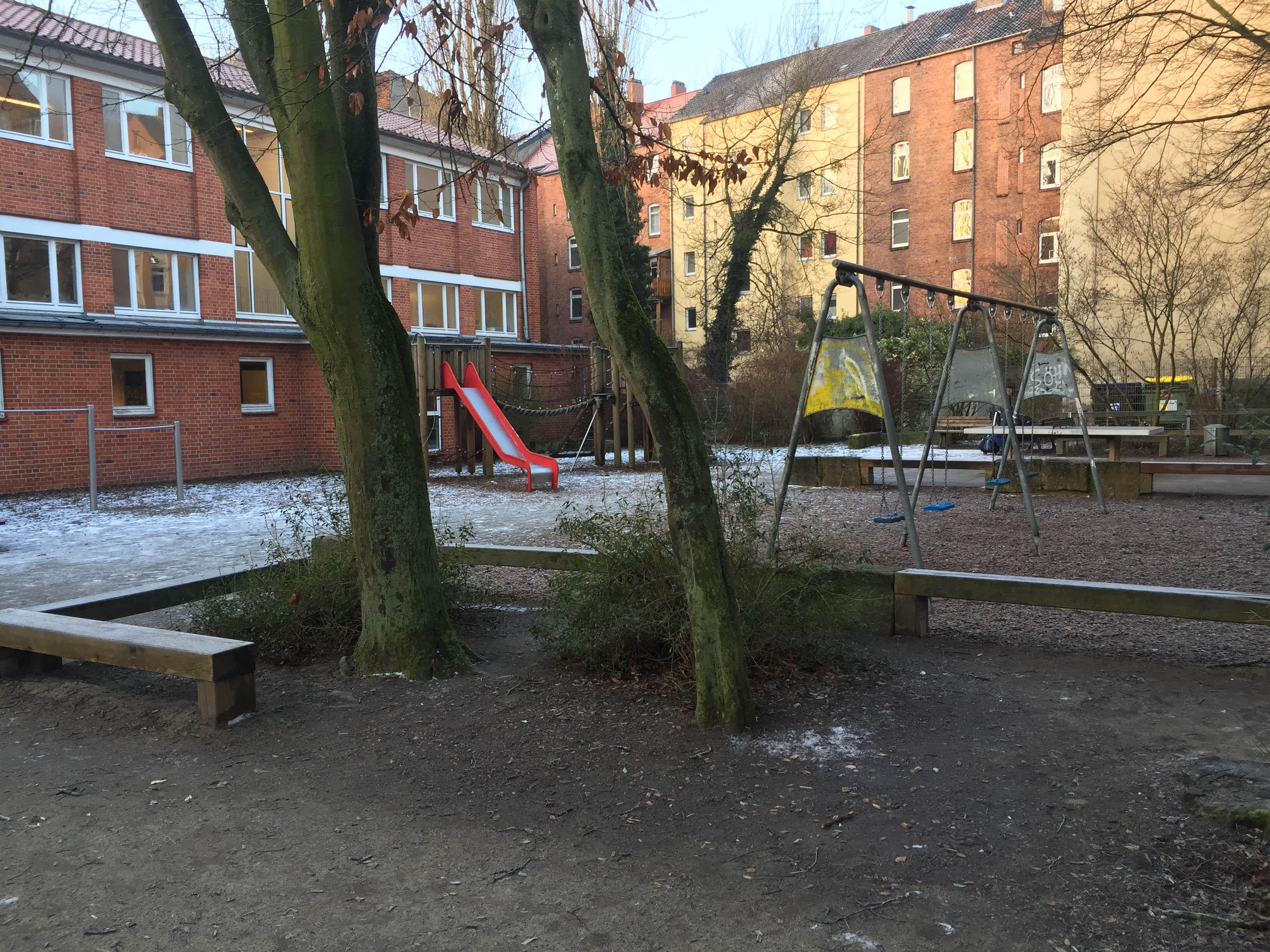 Spielplatz mit Rutsche und Schaukeln.