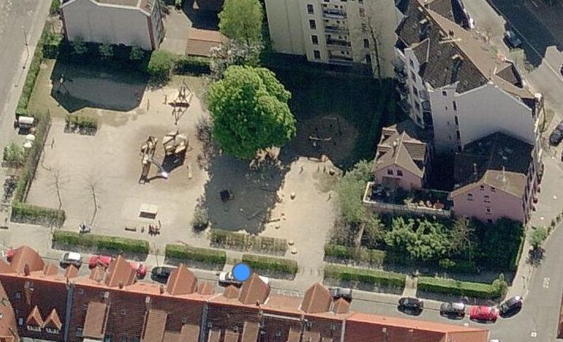 Spielplatz mit Bäumen und Hecken mit Rundumbebauung aus der Luft