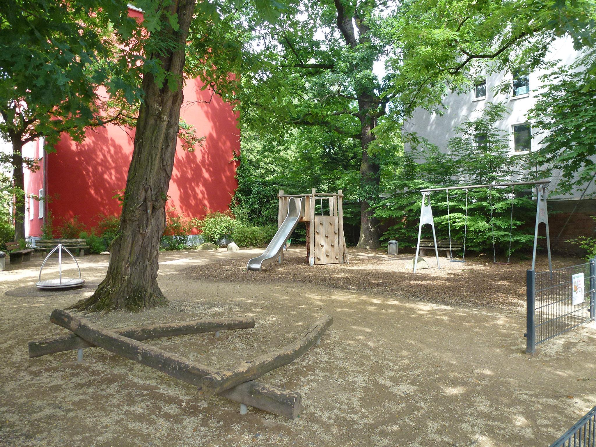 Auf dem Spielplatz Sonnenweg/Rauenstraße zwischen Häusern gibt es unter Bäumen zwei Ruhebänke für Begleitpersonen, eine Kinderrutsche, zwei Schaukeln, einen Drehkreisel und drei übereinandergelegte Baumstämme zum Balancieren.