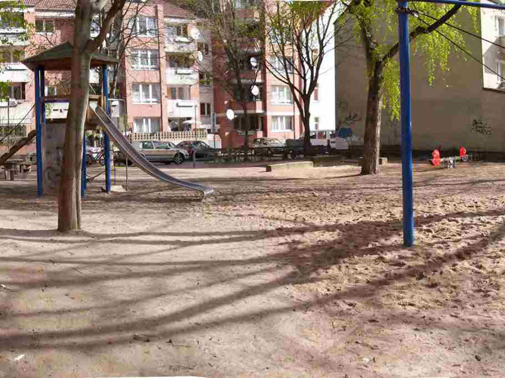 Spielplatz mit Rutsche und Wippe, im Hintergrund Mietshäuser