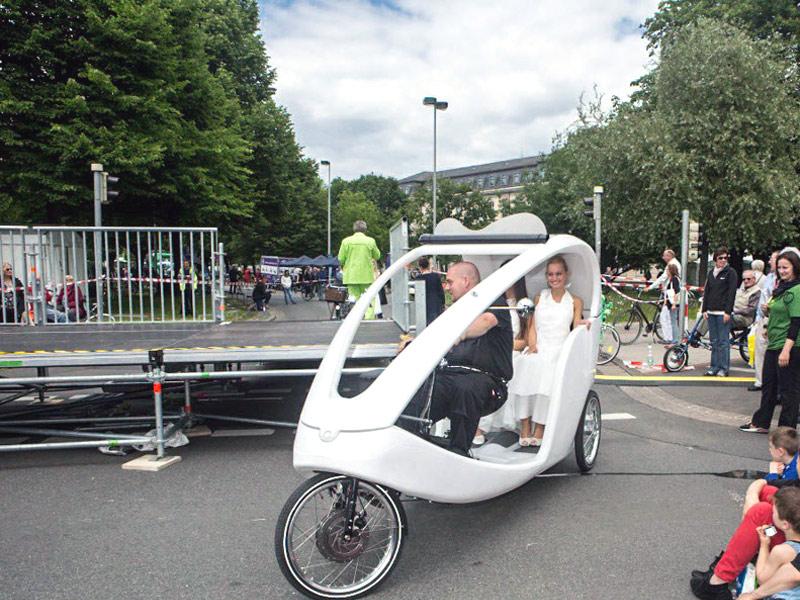 Zwei Frauen lassen sich in einer Fahrrad-Rikscha fahren, Passanten schauen interessiert zu