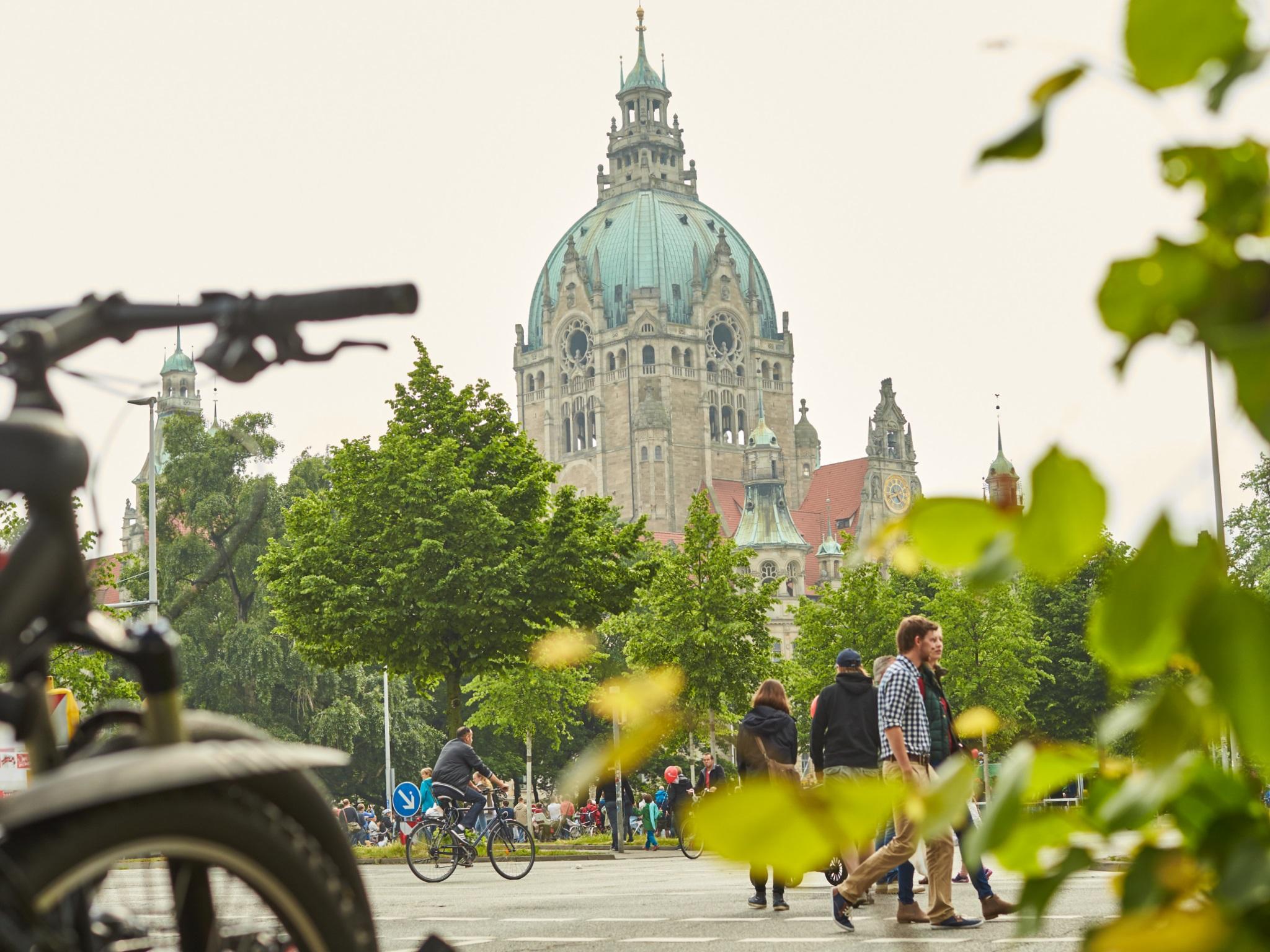 Auf der für den motorisierten Verkehr gesperrten Straße vor dem Hannoverschen Rathaus flanieren Fußgänger und fahren Radfahrer.