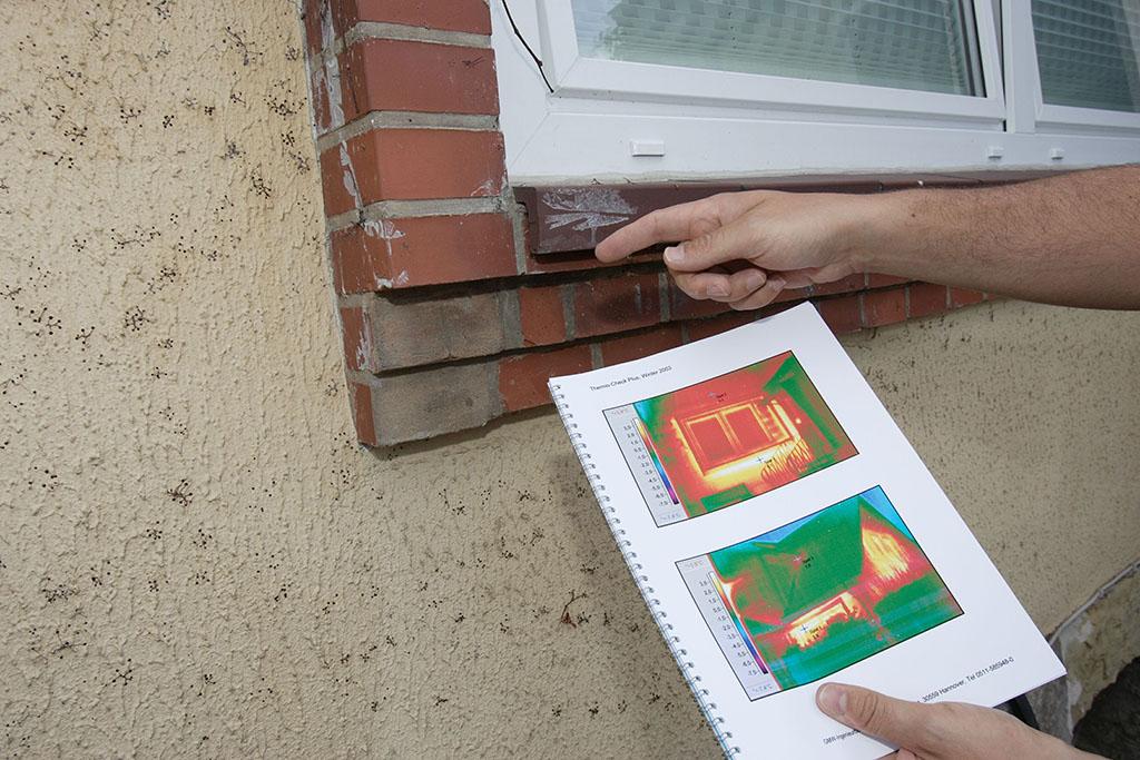 Hände mit Thermografiegerät vor Fenster