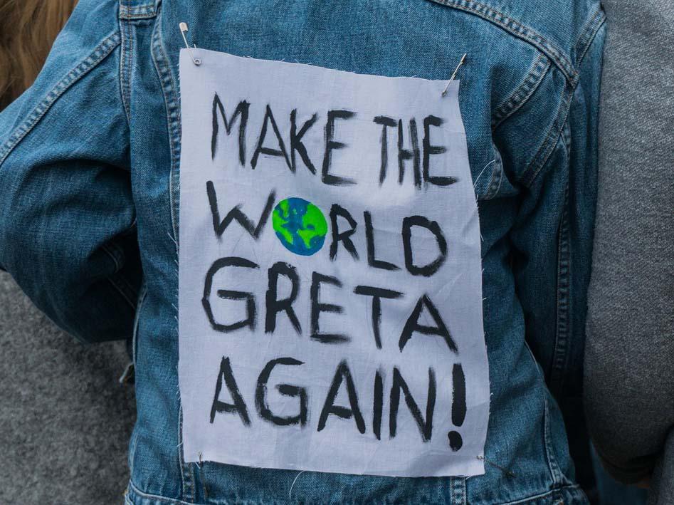 """Eine Person von hinten, die eine Jeansjacke steht. Darauf steht """"Make the world Greta again""""."""