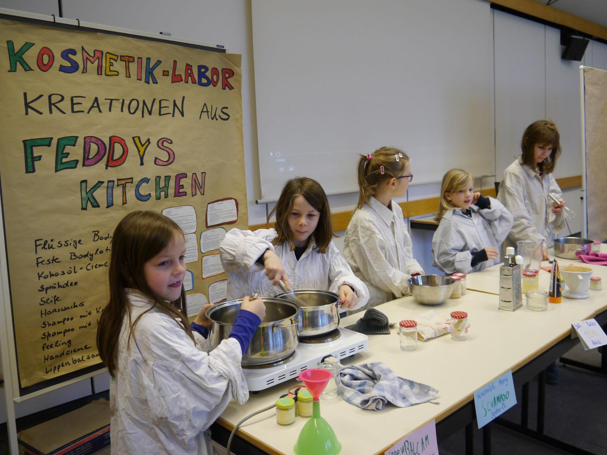 Fünf Kinder im Kittel an Tischen mit Töpfen.