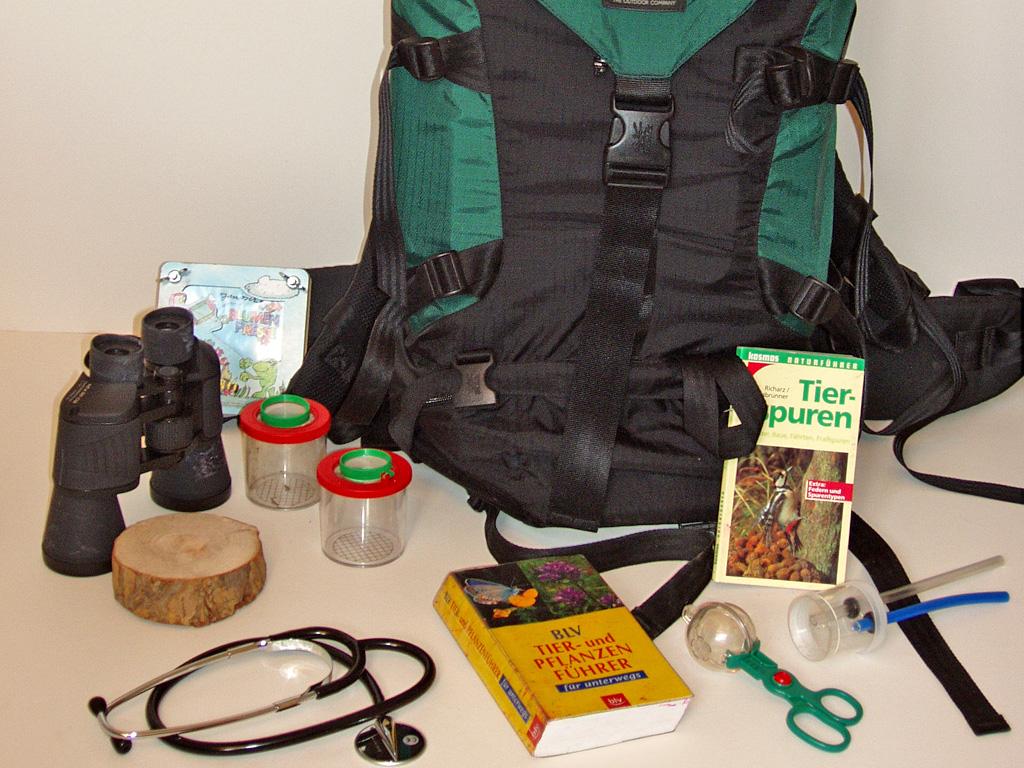 Ein Rucksack mit Büchern, Stethoskop, Fernglas, Probenbehältern und weiteren Erkundungsutensilien