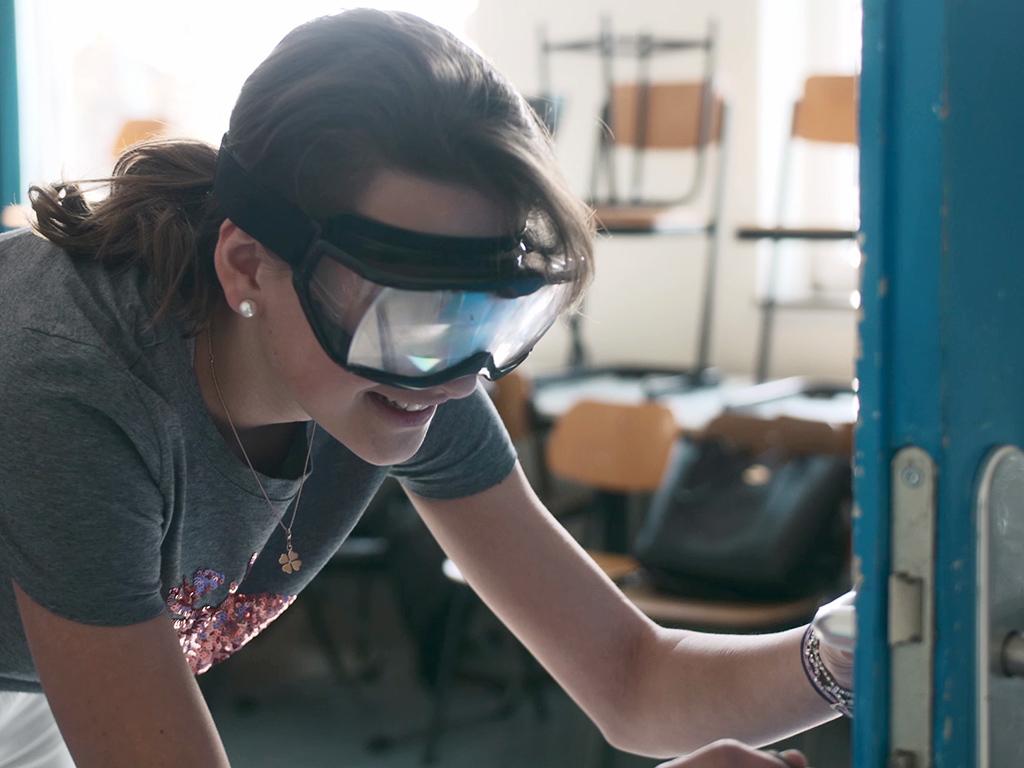 """Ein Mädchen mit einer """"Rauschbrille"""" ertastet eine Türklinke."""