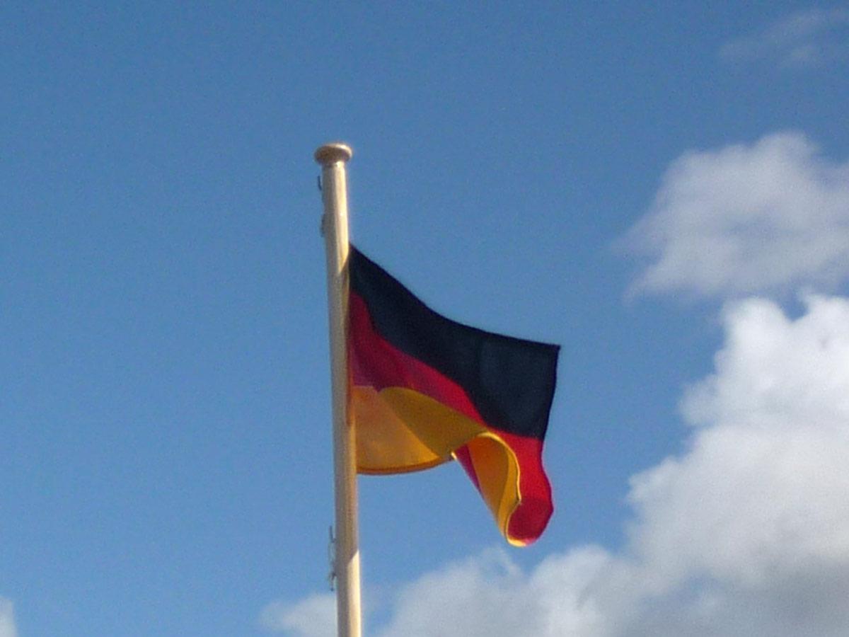 Eine wehende Deutschlandfahne vor blauem Himmel