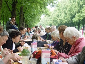 Young and elder people sit at a long dining table for a collective meal