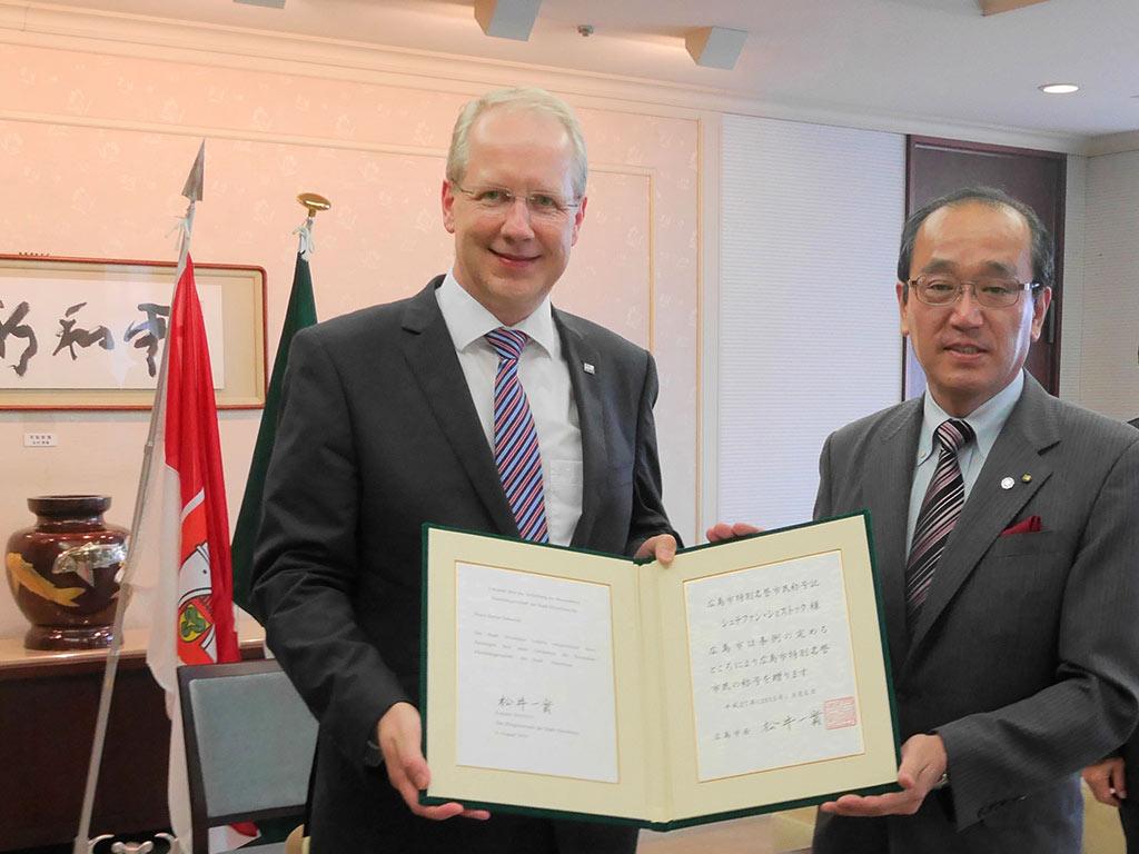 Oberbürgermeister Stefan Schostok und Bürgermeister Kazumi Matsui halten eine Urkunde