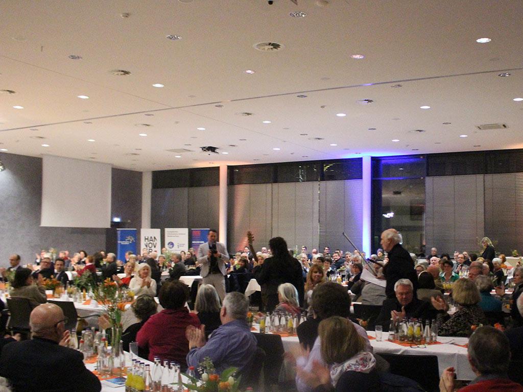 Publikum an langen Tischreihen applaudiert Musikern
