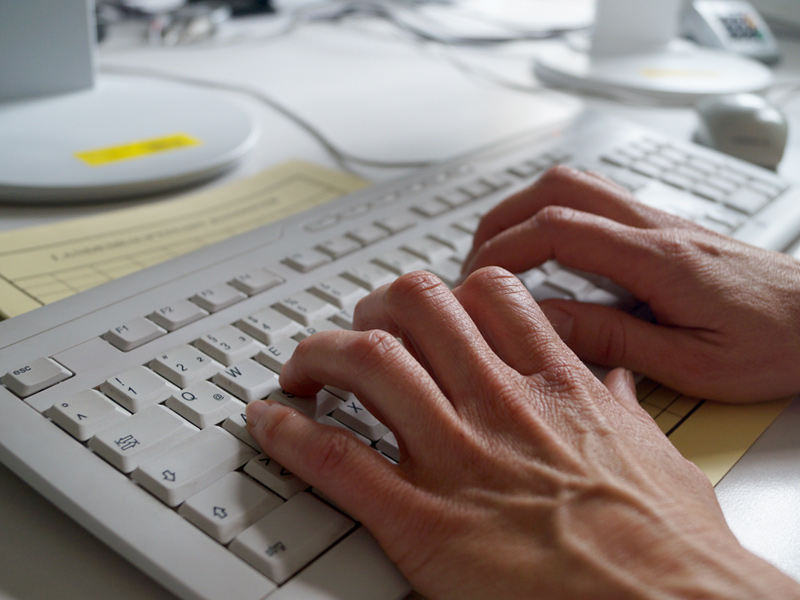Hände auf einer Computer-Tastatur
