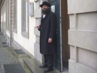 Ein Mann mit Bart steht vor einer Tür.