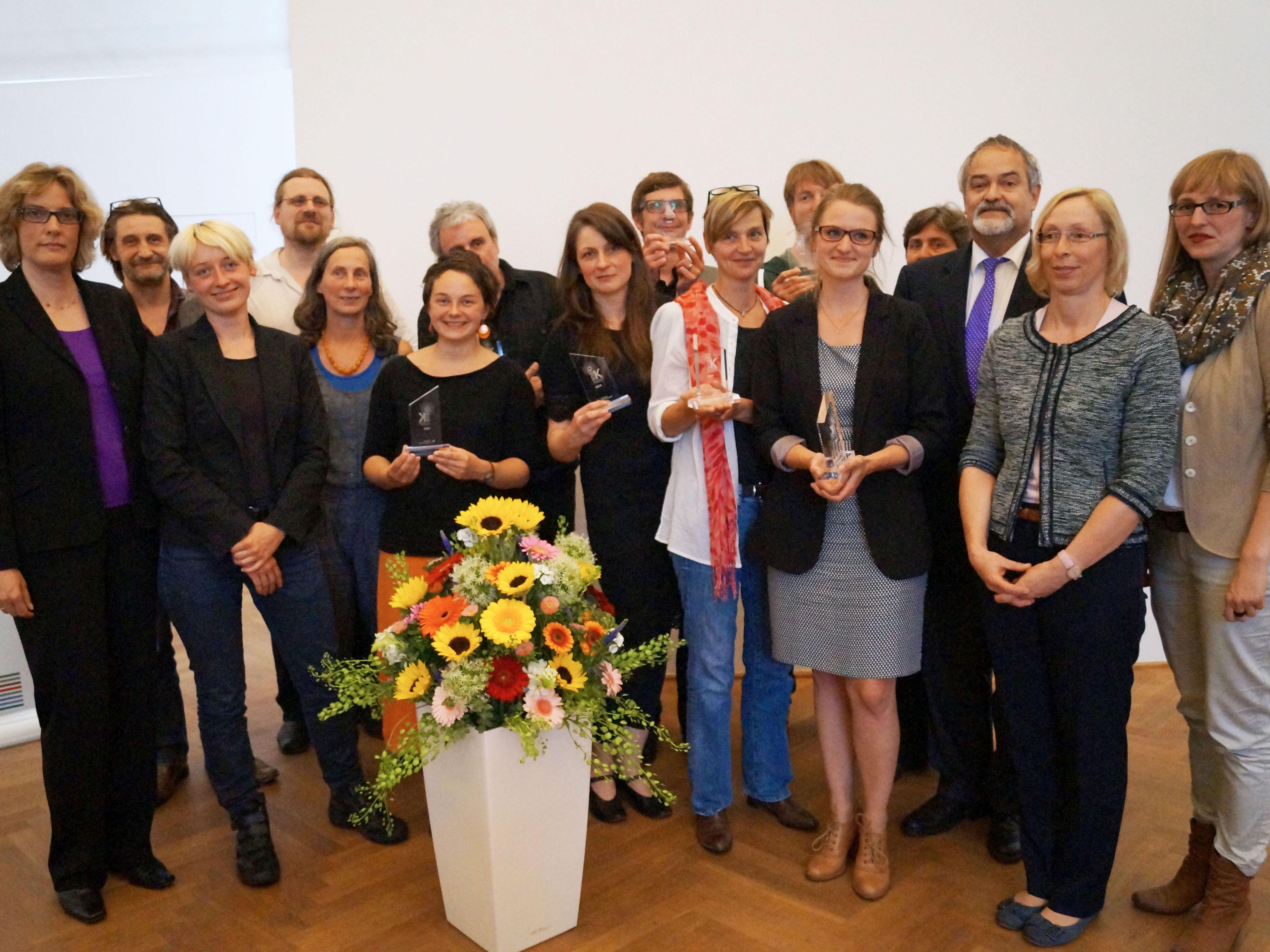 Eine Gruppe von Menschen vor einem Blumenkübel, sieben von ihnen halten eine Trophäe in der Hand.