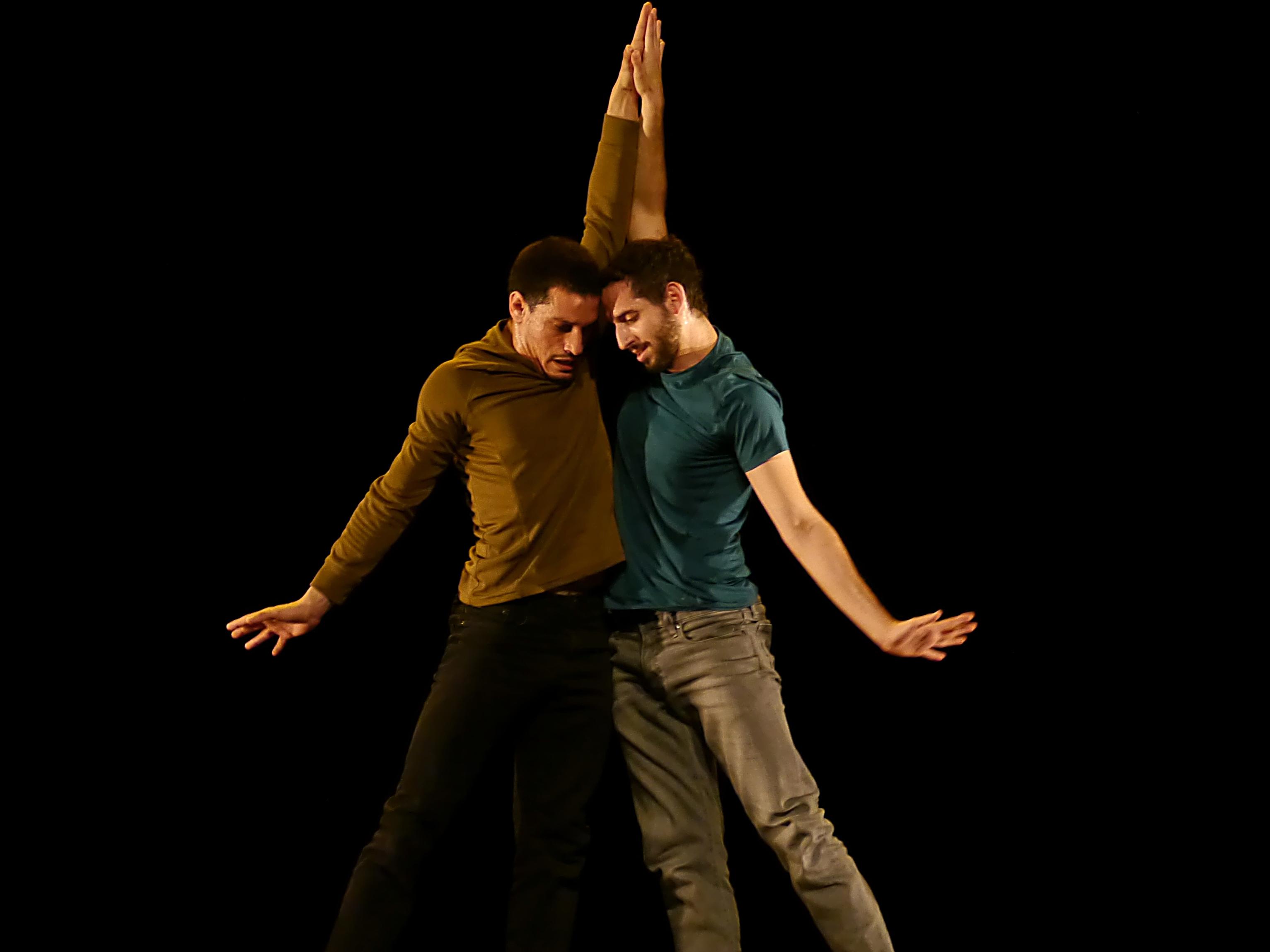Zwei Männer auf einer Bühne, die sich an den Händen halten.