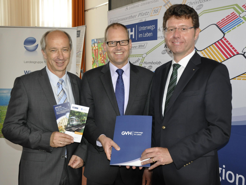 Drei Männer halten Broschüren zum Thema JobCard und Großraumverkehr Hannover in den Händen, im Hintergrund ist die Grafik des Liniennetzplans der Stadtbahn Hannove zu sehen.
