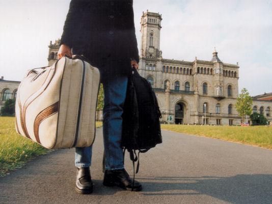 Jemand mit Koffer und Rucksack in der Hand vor einem älteren Gebäude.