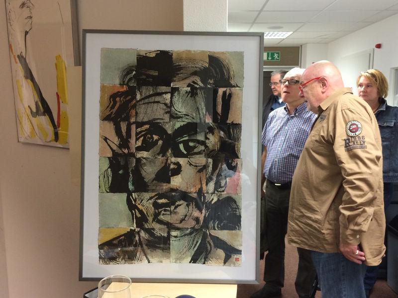 Drei Personen sehen sich ein Gemälde an.
