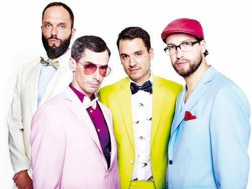 Vier Männer in bunten Anzügen.