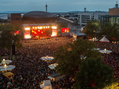 An outdoor space with a huge crowd in front of a large stage.
