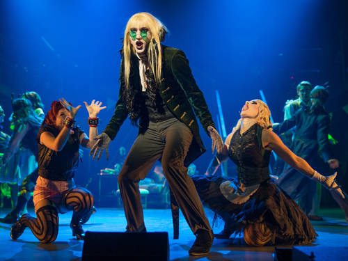 A stage with a man with long blond hair and green glasses in a black velvet coat  and two women in lascivious poses