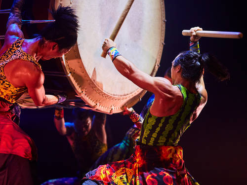 One man holding and another beating a large drum with rather long and thick sticks.