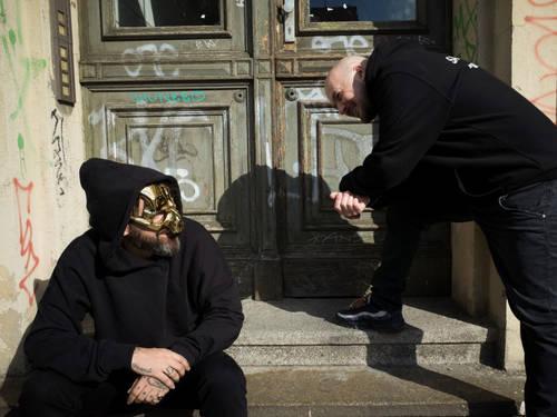 Zwei Männer, einer trägt eine goldene Maske, vor einem Hauseingang.