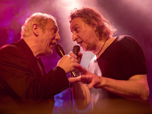 Zwei Männer stehen sich gegenüber und singen gemeinsam.