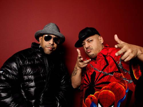 Zwei Männer mit Hip-Hop-Sachen posieren vor rotem Hintergrund.