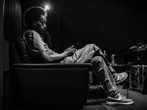Ein Mann mit Afro sitzt auf einem Sofa und hat sein Handy in der Hand.