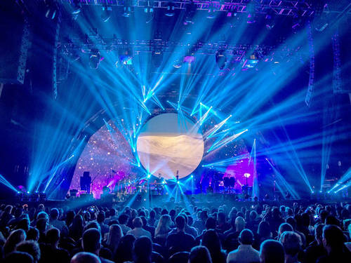 A large crowd in front of a stage with a huge round object and spectacular lighting.