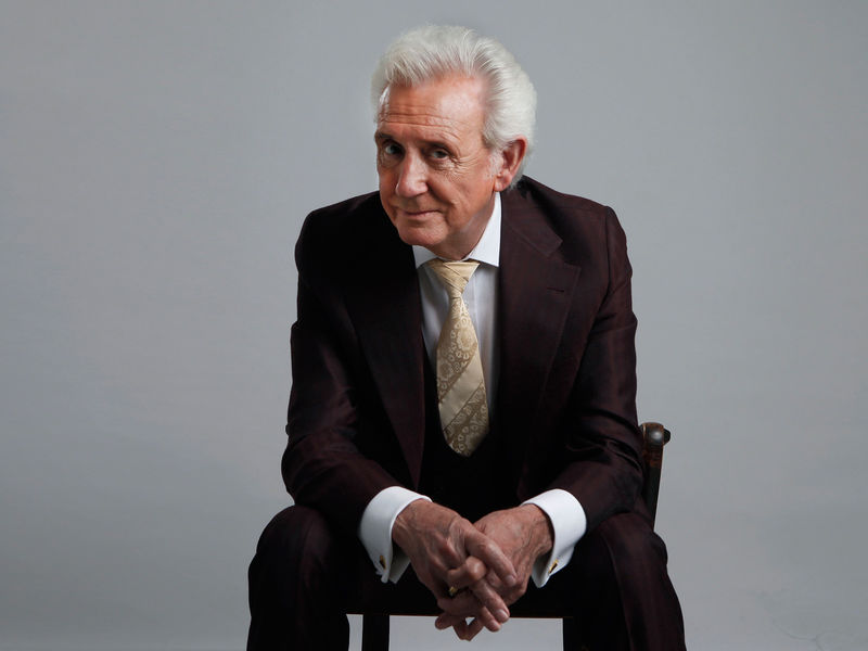 A white-haired man in suit, shirt and tie is sitting on a chair with his hands folded between his knees