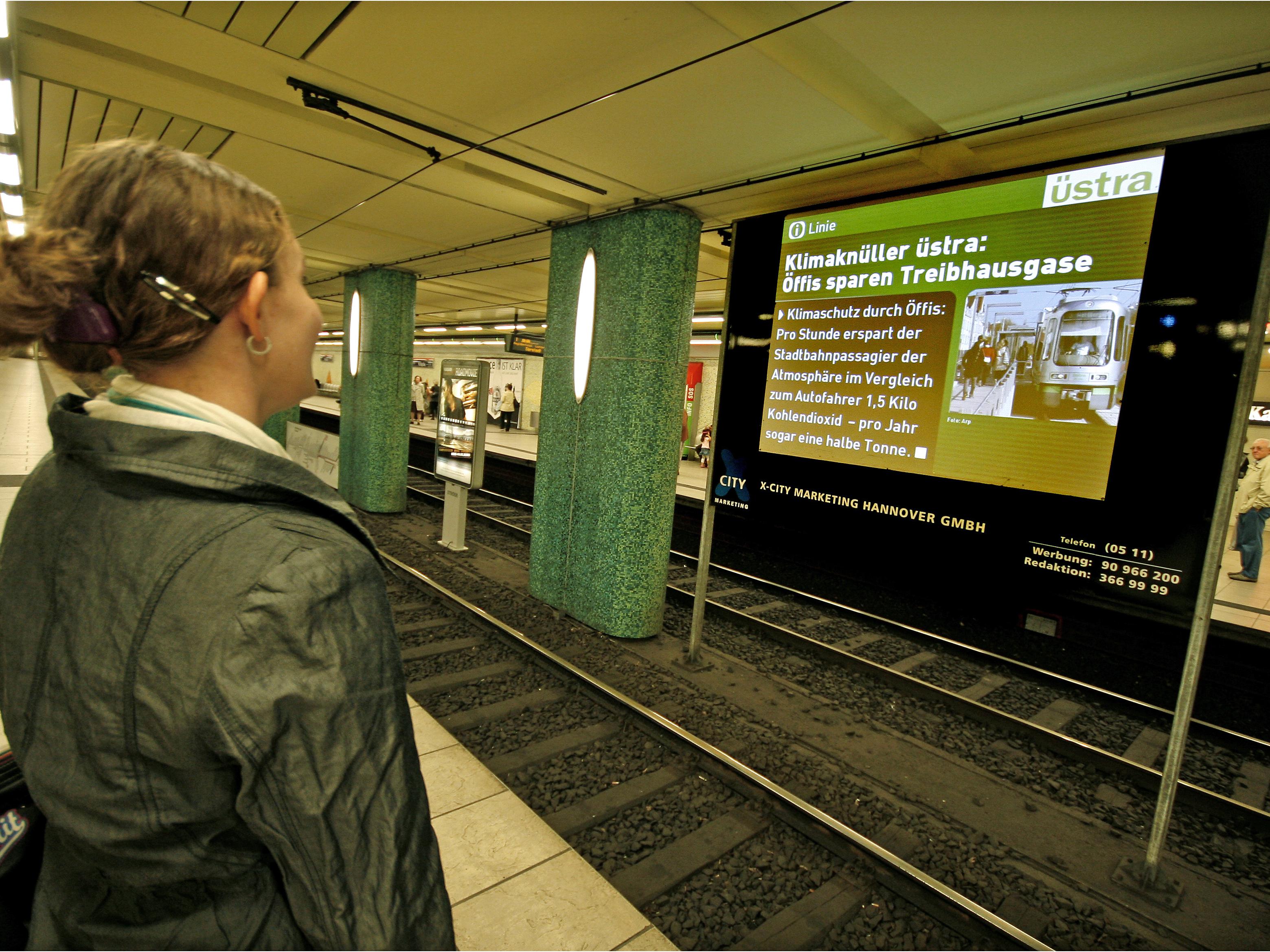 Frau sieht sich eine Nachricht auf einer Leinwand in einer U-Bahnstation an.